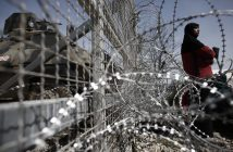 epa05248140 A refugee woman is seen through barbed wirefence during a protest demanding the opening of the borders at the border line between Greece and FYROM at the refugee camp of Idomeni, Greece, 07 April 2016. Migrants who refuse to apply for asylum are to be deported to Turkey, in accordance with a tit-for-tat agreement between the European Union (EU) and Turkey on the refugee and migration crisis.  EPA/KOSTAS TSIRONIS