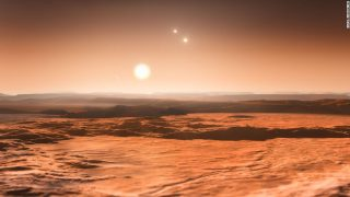 This artist???s impression shows the view from the exoplanet Gliese 667Cd looking towards the planet???s parent star (Gliese 667C). In the background to the right the more distant stars in this triple system (Gliese 667A and Gliese 667B) are visible and to the left in the sky one of the other planets, the newly discovered Gliese 667Ce, can be seen as a crescent. A record-breaking three planets in this system are super-Earths lying in the zone around the star where liquid water could exist, making them possible candidates for the presence of life. This is the first system found with a fully packed habitable zone.