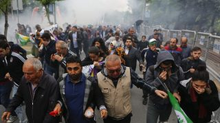 epa05285421 Protestors run away from tear gas after a small clash at the security point at the official place of May Day celebration in Istanbul, Turkey, 01 May 2016. Labor Day or May Day is observed all over the world on the first day of the May to celebrate the economic and social achievements of workers and fight for labourers rights.  EPA/CEM TURKEL