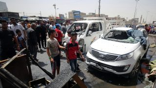 epa05299431 Iraqis inspect the site of a car bomb attack in Baghdad's Sadr city, Iraq, 11 May 2016. According to reports from Iraqi police and hospitals at least 52 people killed and 80 others were wounded in a car bomb attack targeted a crowded market in Sadr city, the Shiite Muslim district of Baghdad.  EPA/AHMED ALI