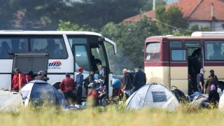 epa05326116 Refugees put their belongings in the buses during a police operation at the makeshift refugee camp near the Greek-Macedonian border town of Idomeni, as pictured from Gevgelia, The Former Yugoslav Republic of Macedonia, 24 May 2016. Greece started the transport of refugees from Idomeni to the new accommodation centres started on 24 May. According to the refugee coordinating committee spokesman Giorgos Kyritsis, all refugees from Idomeni will have been transferred in the next ten days adding that it will be a smooth relocation procedure and not a police sweeping operation.  EPA/GEORGI LICOVSKI