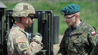 epa05345490 A Polish (R) and a US soldier (L) talk during the Polish-led multinational exercise Anakonda 2016 at the training ground Drawsko Pomorskie, north-western Poland, 04 June 2016. The Polish-led multinational exercise is conducted with allies and partners from 24 countries between 07 and 17 June 2016. The exercise is expected to include 31,000 soldiers, including some 12,000 Polish troops.  EPA/MARCIN BIELECKI POLAND OUT