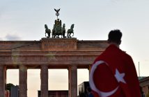 epa05398118 A man with a Turkish flag wrapped around his shoulder stands in front of Brandenburg Gate which is illuminated with the Turkish flag, in Berlin, Germany, 29 June 2016. A Turkish flag was projected onto the Brandenburg Gate in a show of support for Turkey a day after the attacks at Istanbul's Ataturk airport.  EPA/KLAUS-DIETMAR GABBERT