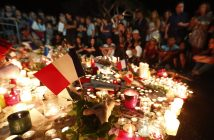 epa05427100 People gather in front of the memorial set on the 'Promenade des Anglais' where the truck crashed into the crowd during the Bastille Day celebrations, in Nice, France, 16 July 2016. According to reports, at least 84 people died and many were wounded after a truck drove into the crowd on the famous Promenade des Anglais during celebrations of Bastille Day in Nice, late 14 July.  EPA/IAN LANGSDON