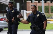 epa05429933 Baton Rouge Police officers signal a car as they stand guard outside of the Our Lady of The Lake Regional Medical Center in Baton Rouge, Louisiana, USA, 17 July 2016, where the injured in a shooting are reportedly being treated. Three police officers were shot dead and others were wounded in Baton Rouge as they responded to a call of shots fired when they were attacked by at least one gunman.  EPA/DAN ANDERSON