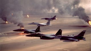 F-16A Fighting Falcons and F-15C and F-15E Eagles fly over burning oil fields during Desert Storm. Operation Desert Storm began Jan. 17, 1991.