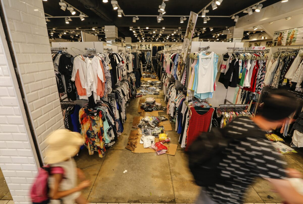 epa05416340 People walk past a garment store affected by super typhoon Nepartak in Taitung County, southeastern Taiwan, 09 July 2016. Nepartak, which swept across Taiwan on 08 July 2016, left three dead and 285 injured and caused significant infrastructure damages. EPA/RITCHIE B. TONGO