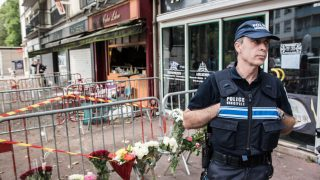 epa05458121 Flowers lay outside the 'Au Cuba Libre' bar as a police man keeps guard, in Rouen, northern France, 06 August 2016. In the early hours of 06 august a fire broke out at a birthday party in the lower level of the bar. At least 13 people were killed and six injured in the fire.  EPA/CHRISTOPHE PETIT TESSON