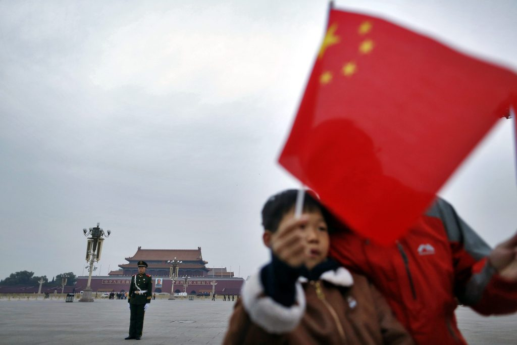 epa05620623 A Chinese paramilitary officer stands guard as Chinese tourists pose for photos with a Chinese national flag on Tiananmen Square near the Great Hall of the People where the 24th Session of the 12th National People's Congress (NPC) Standing Committee meeting is held in Beijing, China, 07 November 2016. According to media reports, Beijing's top legislative body, the NPC Standing Committee has unanimously passed its interpretation of Article 104 of the Basic Law, which states that lawmakers must swear allegiance to Hong Kong as part of China when they take office. Beijing decided to intervene after two pro-independence lawmakers in Hong Kong, Sixtus Baggio Leung Chung-hang and Yau Wai-ching, refused to pledge allegiance to the Hong Kong constitution and swore featly to the Hong Kong nation instead. EPA/HOW HWEE YOUNG