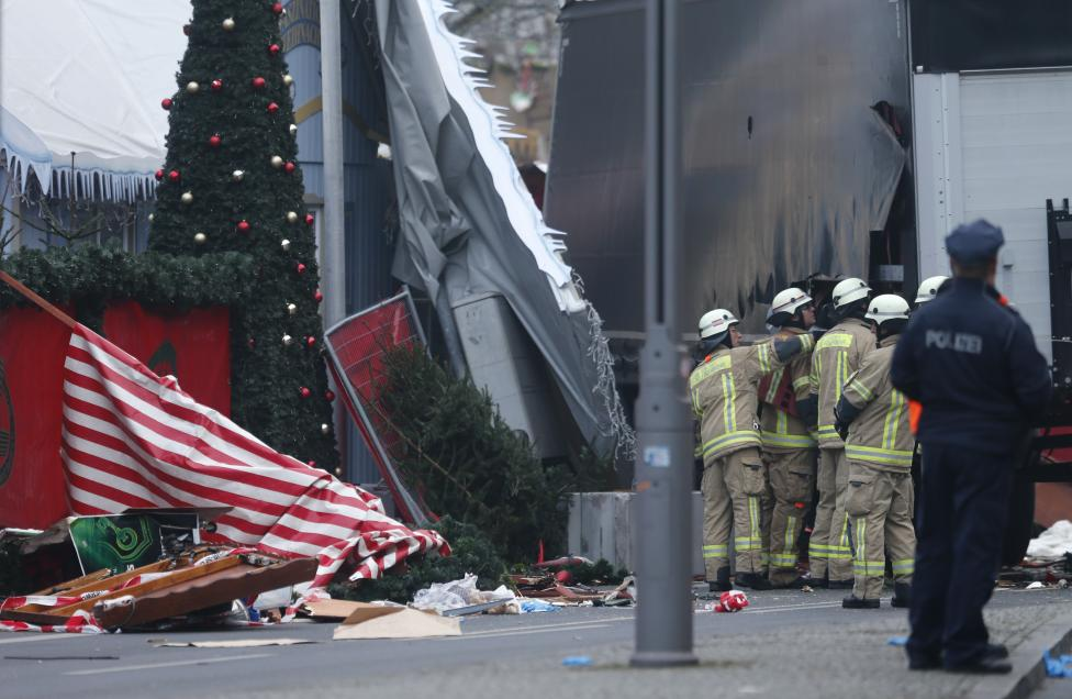 Police and fire fighters stand beside the truck. REUTERS/Hannibal Hanschke