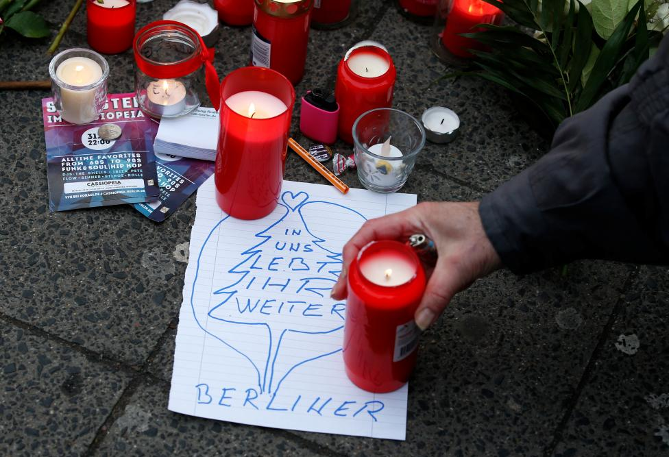 """A man lights a candle near the scene. The note reads """"In us you continue living - Berliner"""". REUTERS/Fabrizio Bensch"""