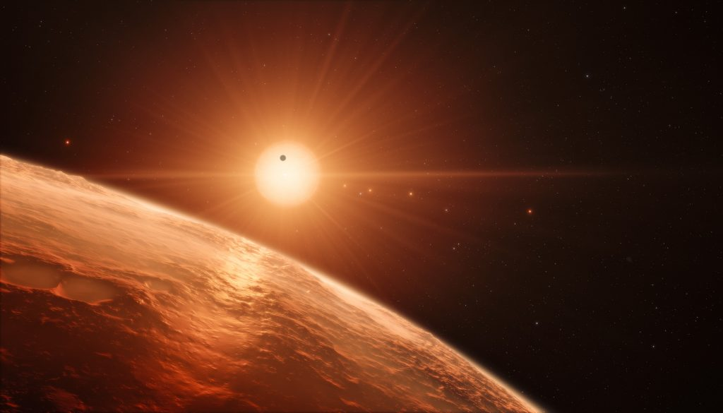 This artist's impression shows the view from the surface of one of the planets in the TRAPPIST-1 system. At least seven planets orbit this ultra cool dwarf star 40 light-years from Earth and they are all roughly the same size as the Earth. They are at the right distances from their star for liquid water to exist on the surfaces of several of them. This artist's impression is based on the known physical parameters for the planets and stars seen, and uses a vast database of objects in the Universe.