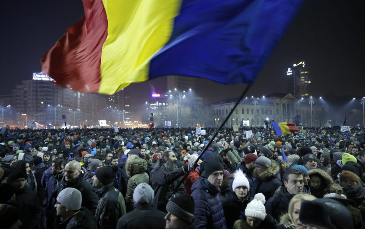 epaselect epa05763814 A Romanian man waves large-scale of the national flag as people shout anti-government slogans during a protest rally in front of government headquarters in downtown Bucharest, Romania, late 31 January 2017. Up to 12,000 people gathered in front of the government headquarters in Romania's capital to protest against a government's emergency ordinance decriminalizing official misconduct and changing the criminal law, media reported. The emergency decree was announced in the late hours of 31 January triggering a massive protest outside the government's building as protesters said that the ordinance will weaken anti-graft efforts. Another government decree would grant prison pardons for several offences, media added.  EPA/ROBERT GHEMENT
