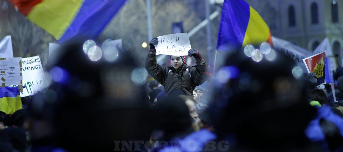 epa05765503 People wave flags and shout anti-government slogans during a protest rally in front of government headquarters in Bucharest, Romania, 01 February 2017. Up to 100,000 people gathered in front of government building and block the city traffic to protest against a government bill, that passed trough government session late 31 January, as a government ordinance to pardon those sentenced to jail terms shorter than five years, in the light that many Romanian parliament and administration members are having issues with justice. Other tenth of thousand people, estimated by national TV stations, participate in similar protests in big cities around the country this evening. Protest turned viloent after soccer fans entered the government plaza and charged the riot police with flares and stones.  EPA/ROBERT GHEMENT