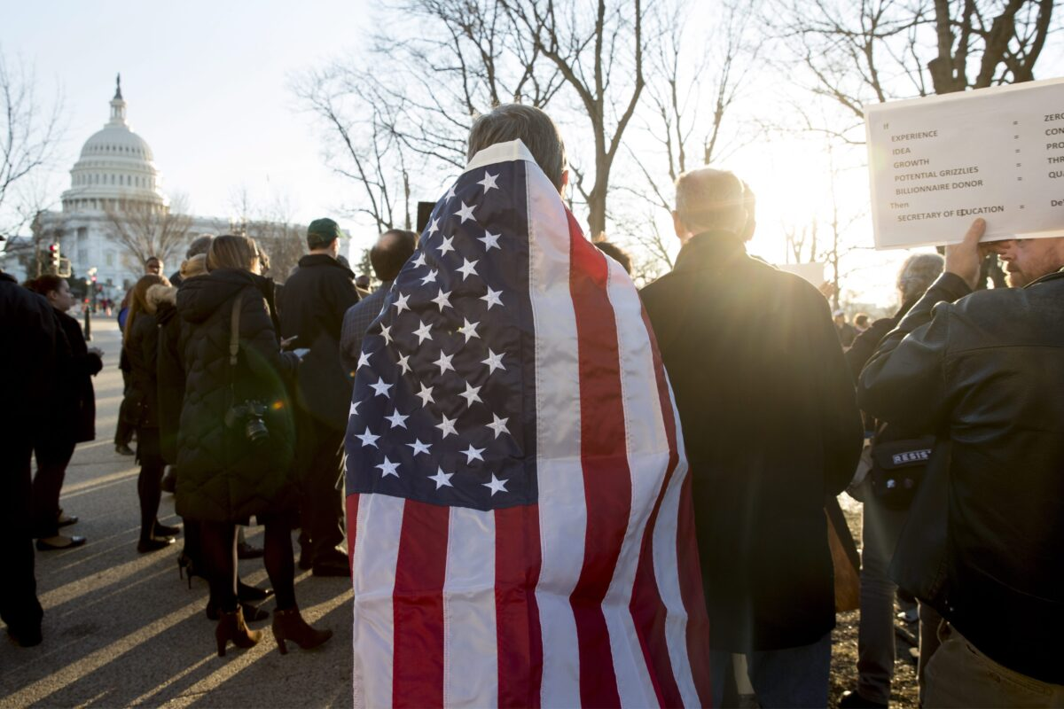 epa05775464 A man wears the US national flag at a rally calling for the US Senate to vote against confirming US President Donald J. Trump's nominee for Secretary of Education, Betsy DeVos, on Capitol Hill in Washington, DC, USA, 06 February 2017. With the Senate split 50-50, Senate Democrats plan to hold the Senate floor for 24 hours before the 07 February vote in an attempt to persuade just one more Republican to vote against the confirmation of DeVos. EPA/MICHAEL REYNOLDS