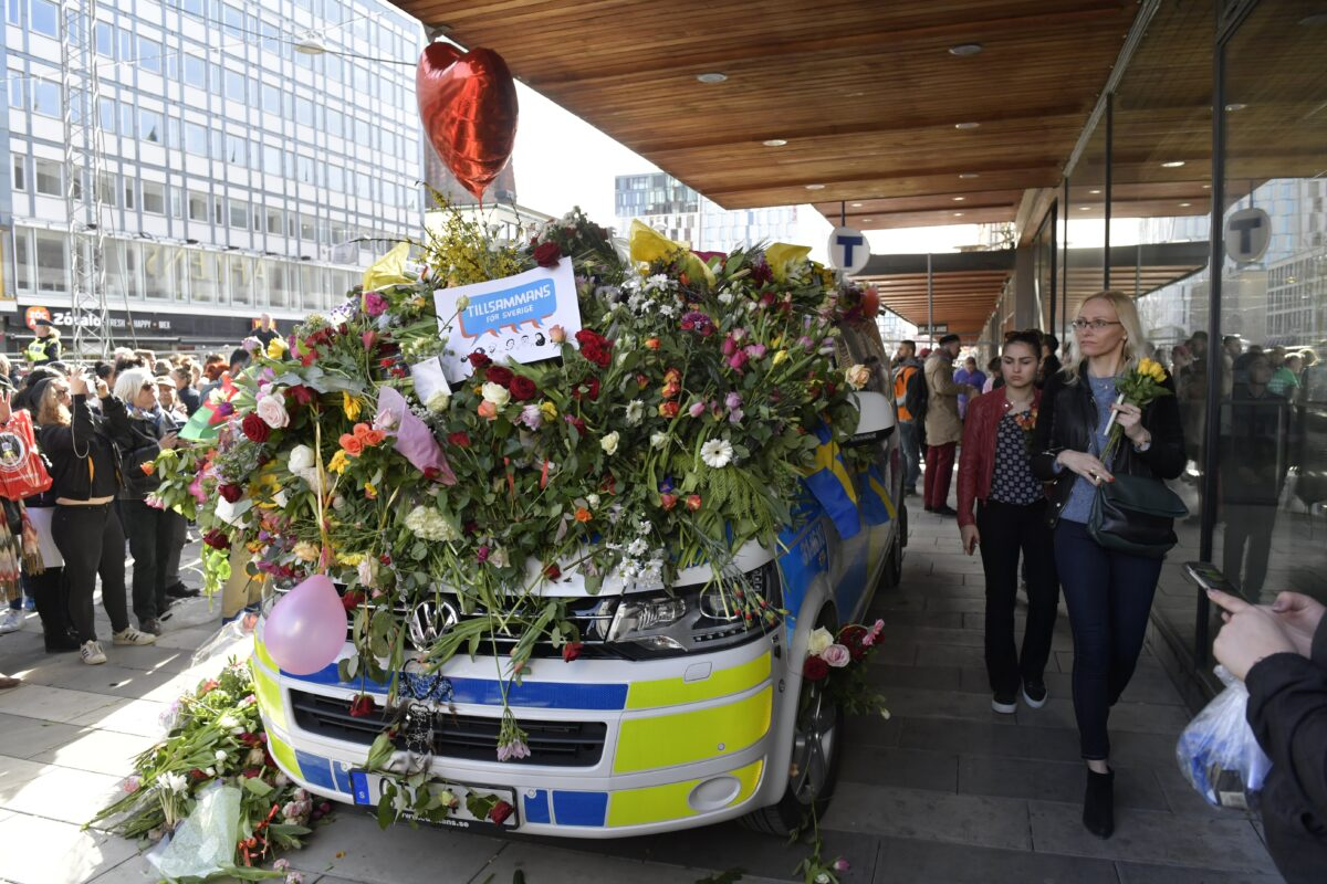 epa05899349 People leaving flowers on a police van in central Stockholm, Sweden, 09 April 2017 following the terror attack on Drottninggatan, central Stockholm. A hijacked beer truck ploughed into pedestrians on Drottninggatan and crashed into Ahlens department store, killing four people, injuring 15 others late 07 April 2017. EPA/JESSICA GOW SWEDEN OUT