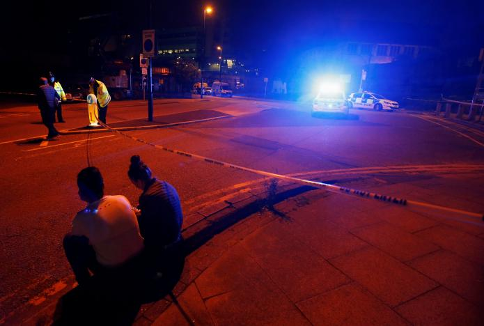 People sit by the side of the road next to a police cordon outside the Manchester Arena, where U.S. singer Ariana Grande had been performing, in Manchester, northern England, Britain, May 23, 2017. REUTERS/Andrew Yates