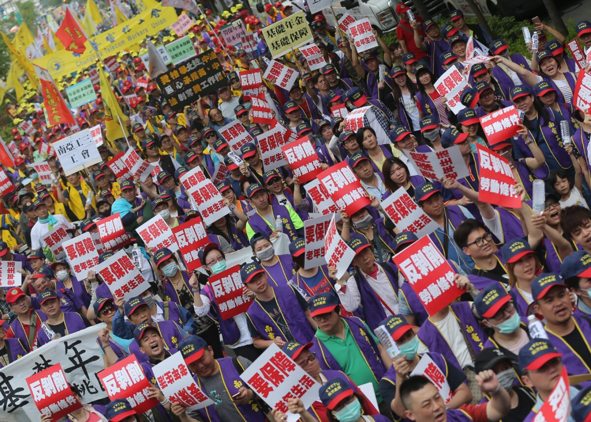 epa05938445 Taiwanese workers march at the street carrying placards marking the International Labor Day in Taipei, Taiwan, 01 May 2017. Thousands of protesters join the protest asking for reform for better workers' condition. EPA/RITCHIE B. TONGO