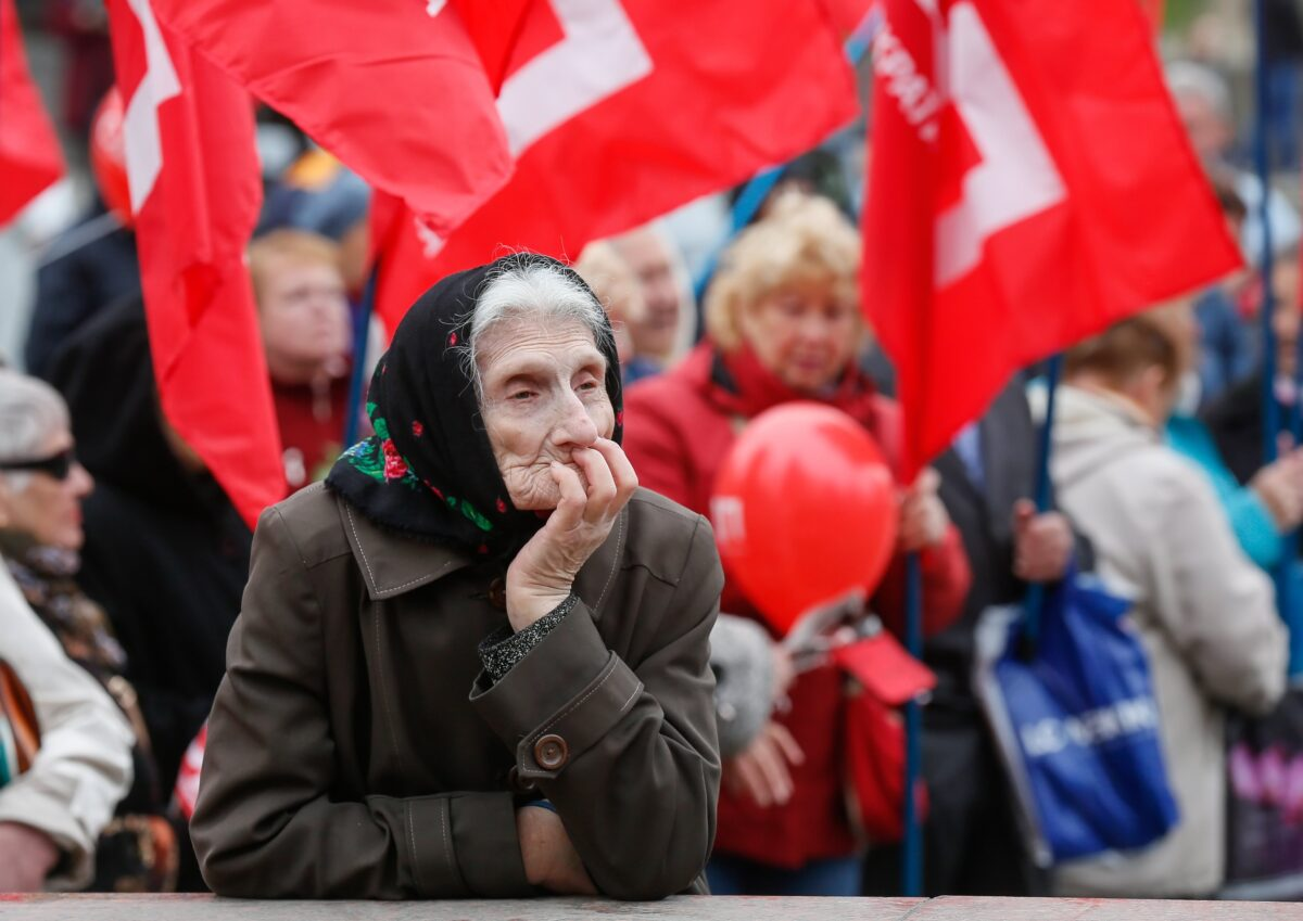 epa05938719 An old woman looks on as supporters of the Ukrainian Socialist and different left-wing parties rally to mark International Labour Day in the center of Kiev, Ukraine, 01 May 2017. Labour Day or May Day is observed all over the world on the first day of May to celebrate the economic and social achievements of workers and fight for labourers rights. EPA/SERGEY DOLZHENKO
