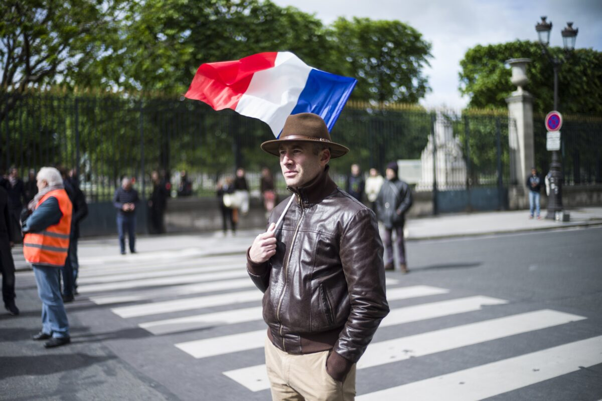 epa05938650 A supporter listens to the speech of Former President of the Front National (FN) far-right party Jean-Marie Le Pen during the rally by the statue of Joan of Arc in Paris, France, 01 May 2017. Labor Day, or May Day, is observed all over the world on the first day of May to celebrate the economic and social achievements of workers and fight for laborers rights. EPA/YOAN VALAT