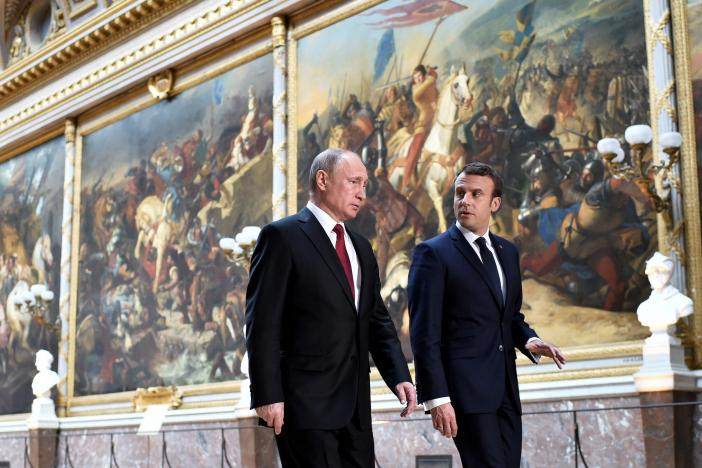French President Emmanuel Macron (R) speaks to Russian President Vladimir Putin (L) in the Galerie des Batailles (Gallery of Battles) as they arrive for a joint press conference at the Chateau de Versailles before the opening of an exhibition marking 300 years of diplomatic ties between the two countries in Versailles, France, May 29, 2017.   REUTERS/Stephane De Sakutin/Pool
