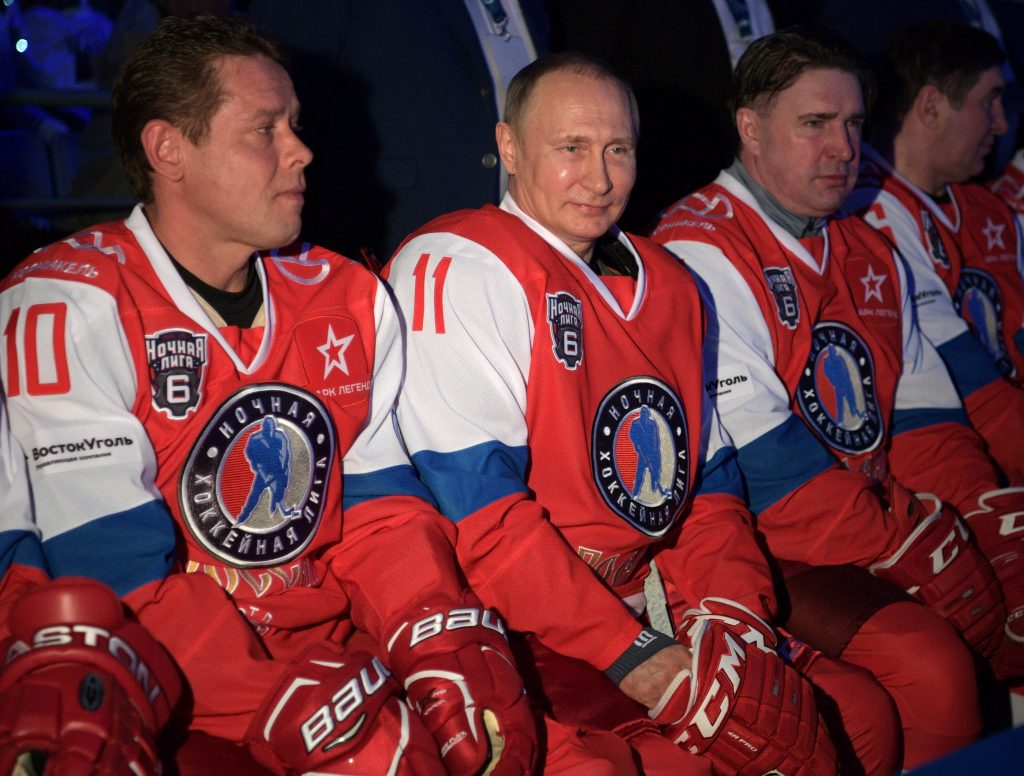 epa05955283 Russian President Vladimir Putin (2-L) sits on the bench prior the gala match of sixth Night Hockey League Festival in Sochi Olympic Park, Russia, 10 May 2017. At left is Pavel Bure former NHL star. EPA/ALEXEI DRUZHININ/SPUTNIK/KREMLIN / POOL MANDATORY CREDIT