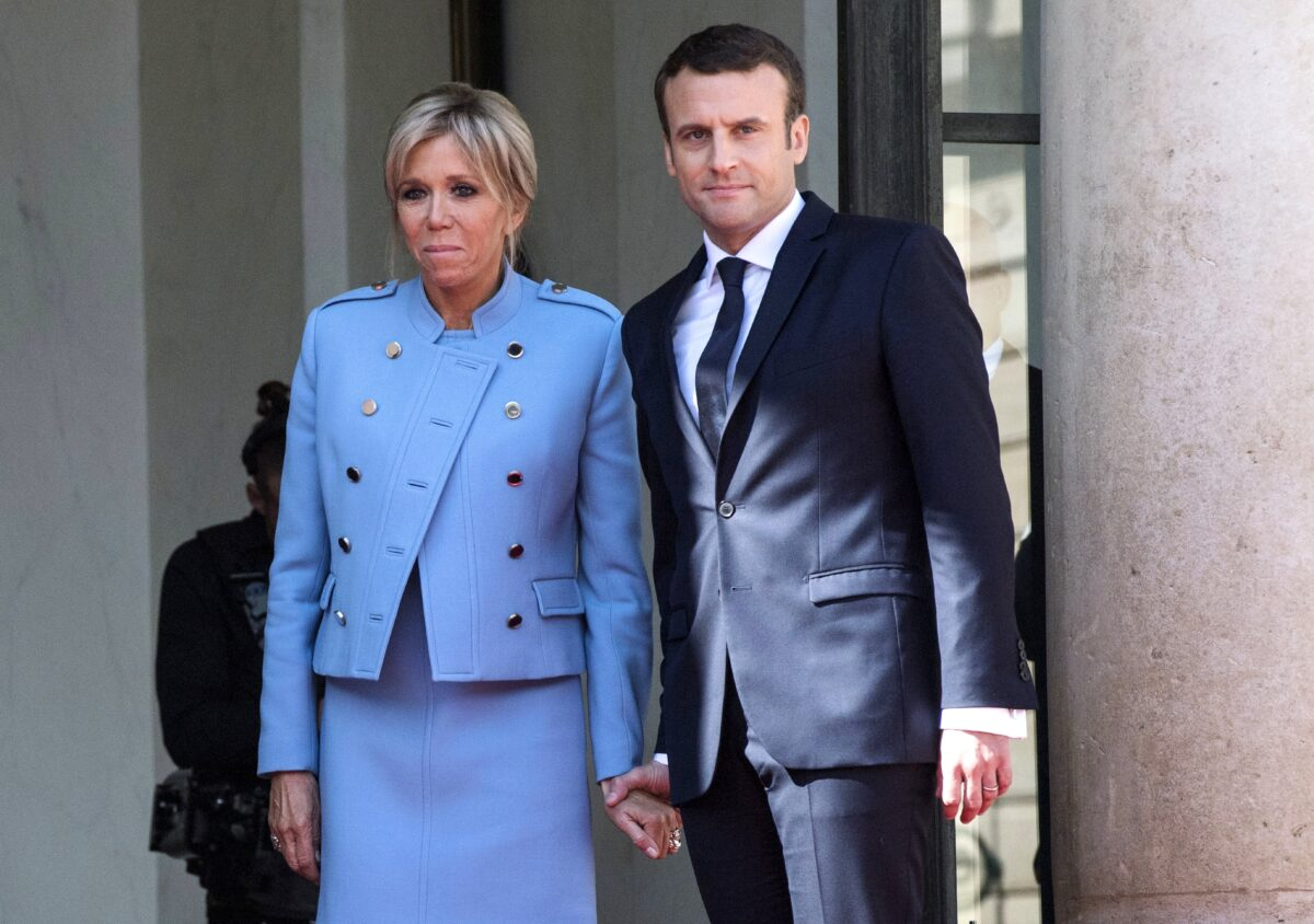 epa05963283 New French President Emmanuel Macron and his wife Brigitte Trogneux watch outgoing French President Francois Hollande (unseen) leaving Elysee Palace after the handover ceremony and prior to Macron's formal inauguration as French President on May 14, 2017 in Paris.  EPA/JULIEN DE ROSA
