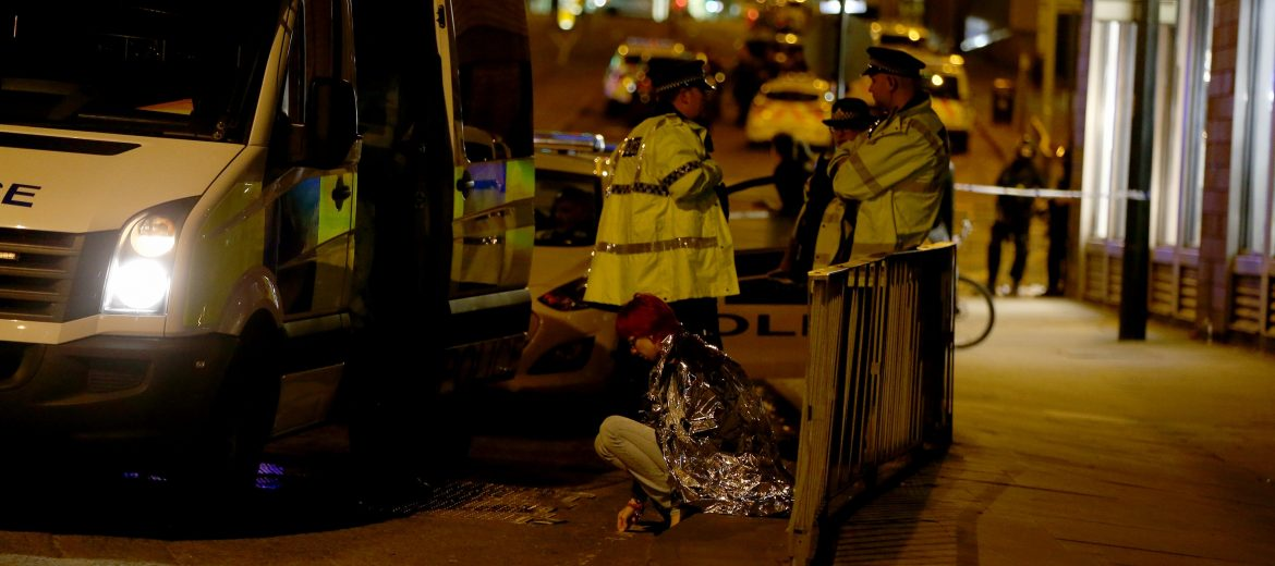 epa05982570 A woman sits in the street in a blanket near the Manchester Arena as police guard the area following reports of an explosion, in Manchester, Britain, 23 May 2017. According to a statement released by the Greater Manchester Police on 23 May 2017, police responded to reports of an explosion at Manchester Arena on 22 May 2017 evening. At least 19 people have been confirmed dead and others 50 were injured, authorities said. The happening is currently treated as a terrorist incident until police know otherwise. According to reports quoting witnesses, a mass evacuation was prompted after explosions were heard at the end of US singer Ariana Grande's concert in the arena.  EPA/NIGEL RODDIS