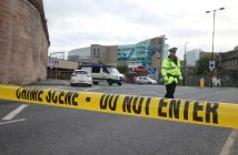 epa05982736 Members of the police stand behind a cordoned off area near the Manchester Arena in Manchester, Britain, 23 May 2017. According to a statement released by the Greater Manchester Police on 23 May 2017, police responded to reports of an explosion at Manchester Arena on 22 May 2017 evening. At least 19 people have been confirmed dead and around 50 others were injured, authorities said. The happening is currently treated as a terrorist incident until police know otherwise. According to reports quoting witnesses, a mass evacuation was prompted after explosions were heard at the end of US singer Ariana Grande's concert in the arena.  EPA/NIGEL RODDIS