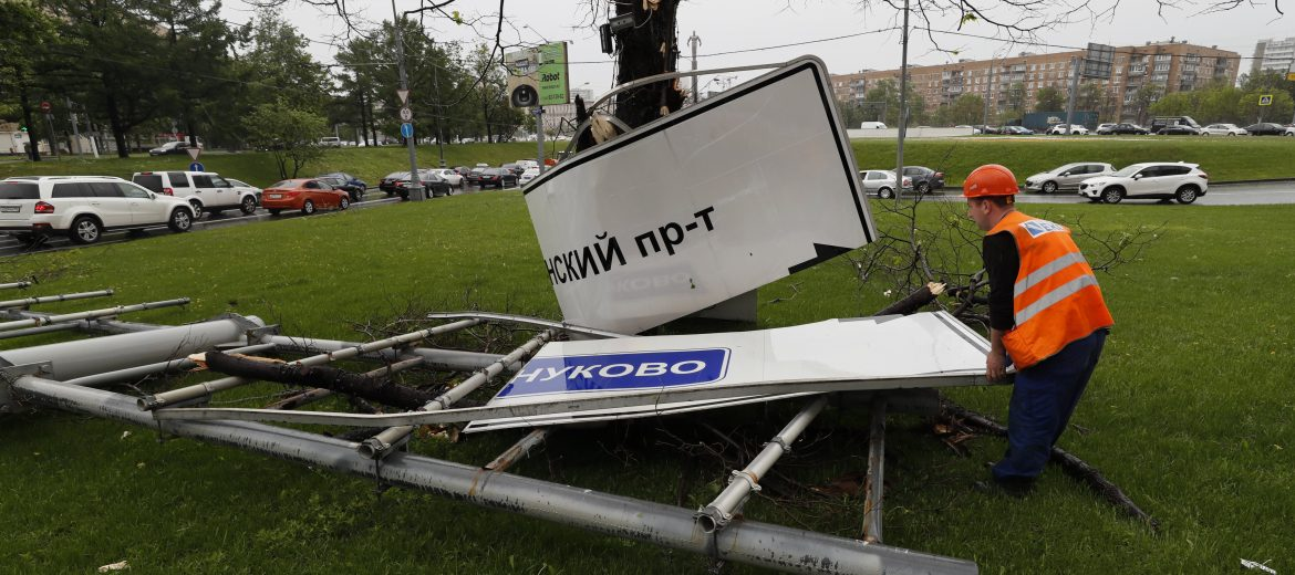 epa05997837 A worker removes a fallen road signpost after a strong thunderstorm in Moscow, Russia, 29 May 2017. Media reports citing a source of the local emergency services state that at least seven people in variouys districts of the Russian capital died by uprooted trees and 'other objects torn down' by the thunderstorm.  EPA/YURI KOCHETKOV
