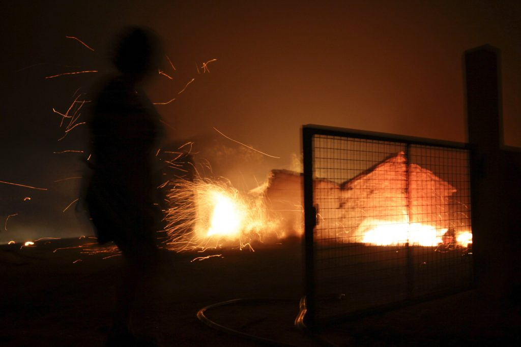 epa06034511 A unidentified local resident, surrounded by sparks, watches his house burning in fire in Figueira, near Pedrogao Grande, Leiria District, Center of Portugal, 17 June 2017. About 180 firemen, 52 land vehicles and 2 planes are fighting to extinguish the fire. EPA/PAULO CUNHA