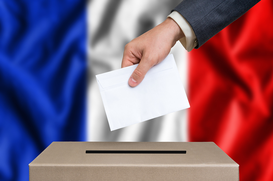 Election in France. The hand of man putting his vote in the ballot box. French flag on background.