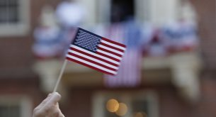 epa06065775 A man waves a United States Flag outside the Old State House, in Boston, Massachusetts, USA 04 July 2017. The United States of America declared independence from Great Britain on 04 July 1776.  EPA/CJ GUNTHER