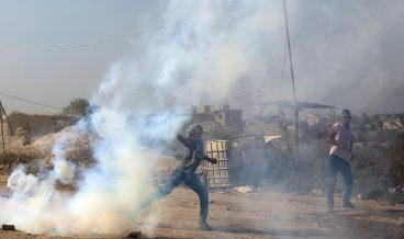 epa06102648 A Palestinian protester throws back a tear-gas cylinder during clashes with Israeli troops near the border with Israel that followed a protest against the security measures at the Al-Aqsa mosque after the Muslim Friday prayer, in the eastern Gaza Strip, 21 July 2017. Israel authorities earlier had installed metal detectors at the entrance to the Al-Aqsa compound after a shooting attack carried out by Israeli Arabs on 14 July against Israeli police during which two Israeli policemen and three attackers were killed. The mufti of Jerusalem had called Palestinian Muslims not to go through the electronic gates and to reject all procedures that change the historic situation of the mosque. The measures reportedly were prohibiting Friday prayers for Muslims at the mosque for the first time in 48 years.  EPA/MOHAMMED SABER