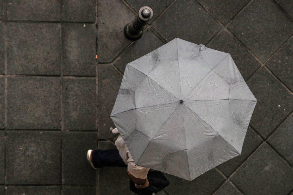 epa06106427 A man walking shelters under his umbrella during a rainy day in downtown Frankfurt Main, Germany, 24 July 2017. EPA/ARMANDO BABANI