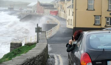 epa06269457 A woman films Storm Ophelia battering the Atlantic coast of Ireland in Lahinch village, County Clare Ireland Ireland, 16 October 2017. The Irish Meteorological Service Met Eireann has issued a red alert weather warning nationwide as tropical depression Ophelia is due to hit Ireland on 16 October. Counties Galway, Mayo, Sligo and Donegal are set to be worst hit by Ophelia. Public services as transport, schools, creches, colleges, retailers, court services, pharmacies, outpatient clinics have all shut down and more than 140 flights have been cancelled. According to reports Around 120,000 homes and businesses have been left without power.  EPA/AIDAN CRAWLEY
