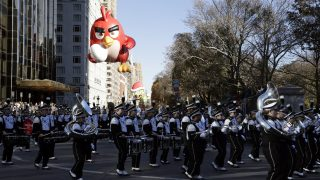 epa06346139 A marching band and The 'Angry Bird' balloon floats down Central Park West during the Macy's 93rd Annual Thanksgiving Day Parade in New York, New York, USA, 23 November 2017. The annual parade, which began in 1924, features giant balloons of characters from popular culture floating above the streets of Manhattan.  EPA/JASON SZENES