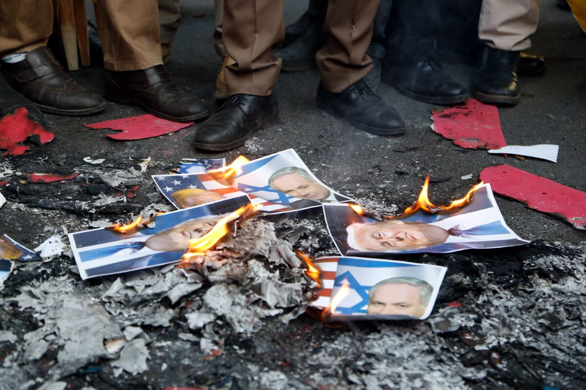 epa06383152 Iranian demonstrators burn posters of US President Donald Trump and Israeli Prime Minister Benjamin Netanyahu during an anti US-Israeli demonstration to show their support to Palestine in Tehran, Iran, 11 December 2017. The protest was held against US President Donald Trump's decision to recognize Jerusalem as the capital of Israel. The demonstrators shouted 'Down with America', 'Down with Israel' and 'Liberation of Jerusalem imminent'. EPA/STRINGER