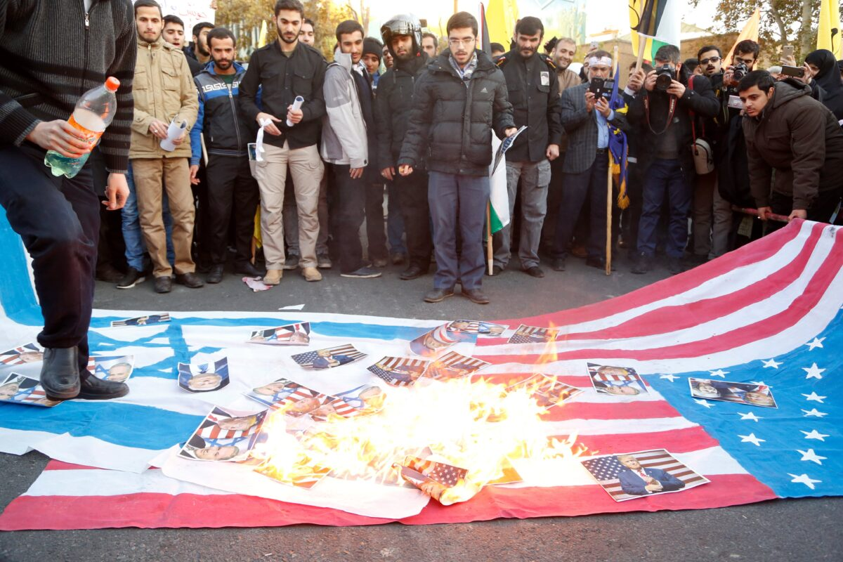 epa06383153 Iranian demonstrators burn posters of US President Donald Trump and Israeli Prime Minister Benjamin Netanyahu along US and Israeli flags during an anti US-Israeli demonstration to show their support to Palestine in Tehran, Iran, 11 December 2017. The protest was held against US President Donald Trump's decision to recognize Jerusalem as the capital of Israel. The demonstrators shouted 'Down with America', 'Down with Israel' and 'Liberation of Jerusalem imminent'. EPA/STRINGER