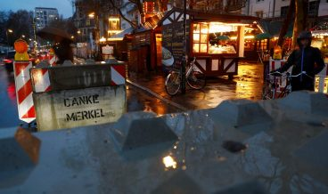 """A concrete barricade with a graffiti treading """"Thank you Merkel"""" blocks the entrance to the Christmas market prior to its official opening in Frankfurt, Germany, November 27, 2017.  REUTERS/Kai Pfaffenbach?"""