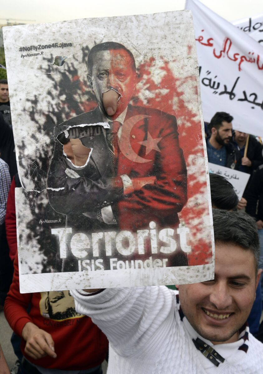 epa06498086 A Kurdish protester carries a placard showing Turkish President Recep Tayyip Erdogan during a protest against what they call the 'Turkish aggression' in northern Syria, near the US embassy in Awkar, east of Beirut, Lebanon, 05 February 2018. The Turkish army is on an operation named 'Operation Olive Branch' in Syria's northern regions against the Kurdish Popular Protection Units (YPG) forces which control the city of Afrin. Turkey classifies the YPG as a terrorist organization.  EPA/WAEL HAMZEH