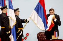 Milorad Dodik, newly elected President of the Republic of Srpska (R) kisses the Bosnian Serb flag, during an official inauguration ceremony at the National Assembly in Western-Bosnian town of Banja Luka, on November 15, 2010. AFP PHOTO MILAN RADULOVIC