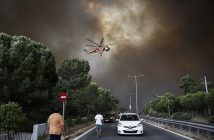 epa06906634 A firefighting helicopter flies over an avenue during a forest fire in Neo Voutsa, a northeast suburb of Athens, Greece, 23 July 2018. After the wildfire in Kineta a second wildfire broke out in the Penteli Mountain. Two major forest fires were raging out of control on either side of the Greek capital Monday, burning houses, prompting residents to flee and turning the sky over Athens a hazy orange from the smoke.  EPA/ALEXANDROS VLACHOS