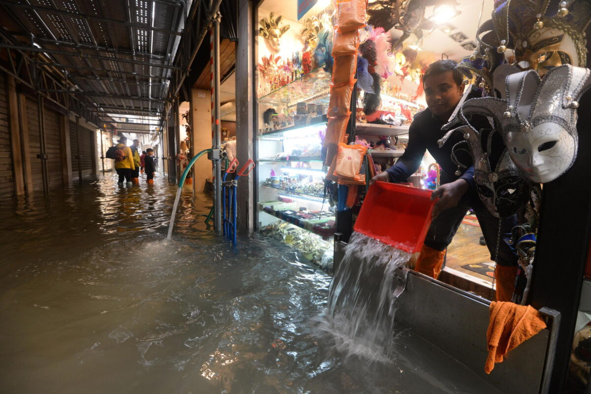 epa07129425 A shopkeeper tries to stop the water that invades the store, in Venice, Italy, 29 October 2018. The high tide reached 149 centimeters above sea level. 70 percent of the historic center is flooded. EPA/Andrea Merola