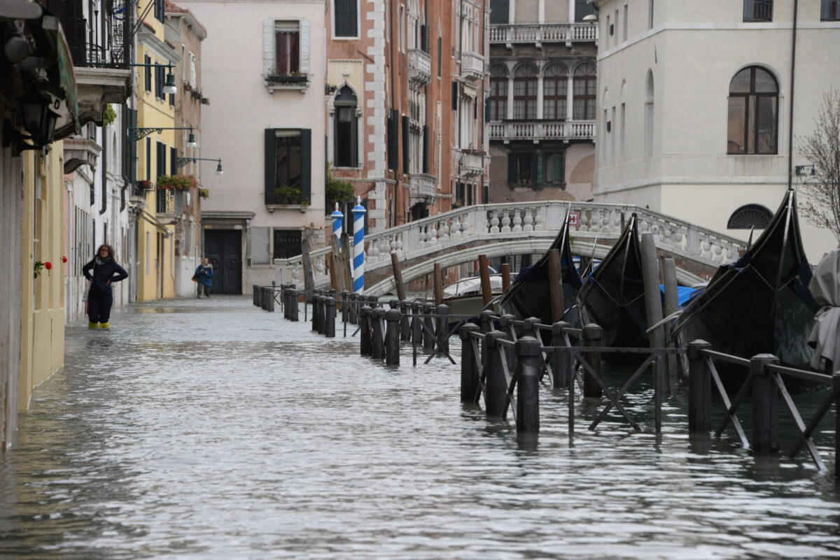 epa07129493 Tourists wander in high water in Venice, Italy, 29 October 2018. The tide reached 149 centimeters above sea level. 70 percent of the historic center is flooded. EPA/ANDREA MEROLA