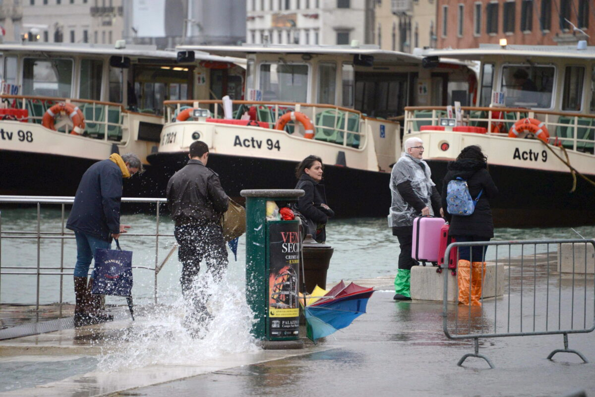 epa07129653 Tourists wander in high water in Venice, northern Italy, 29 October 2018. The tide reached some 149 centimeters above the sea level, with 70 percent of the historic center being flooded. EPA/ANDREA MEROLA