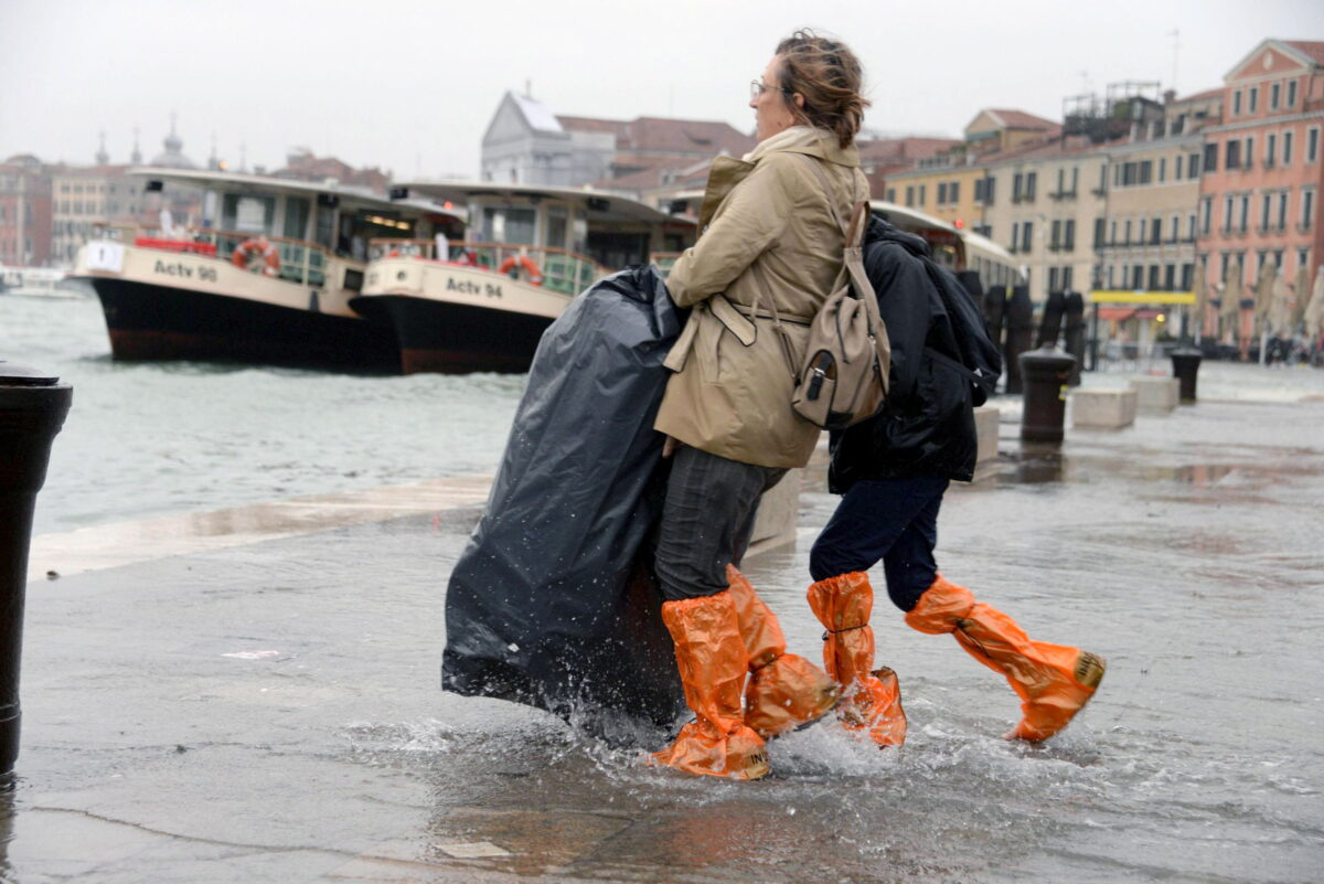 epa07129652 Tourists wander in high water in Venice, northern Italy, 29 October 2018. The tide reached some 149 centimeters above the sea level, with 70 percent of the historic center being flooded. EPA/ANDREA MEROLA