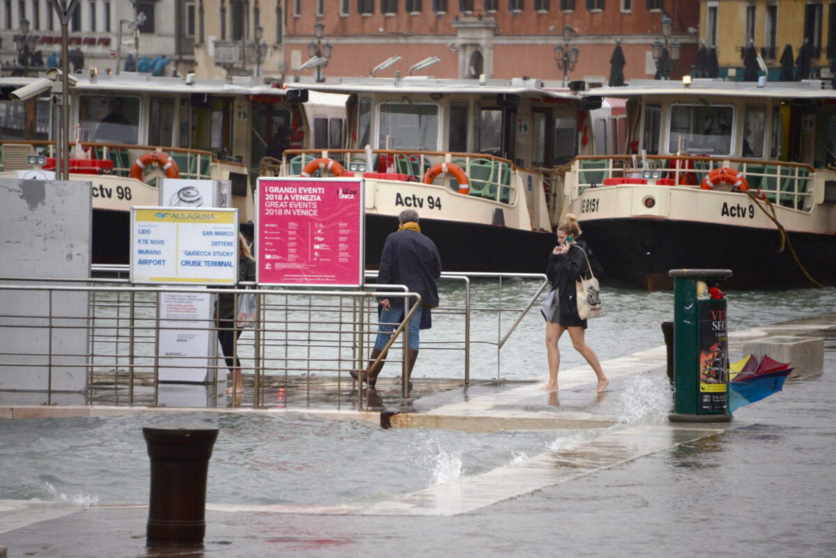 epa07129654 Tourists wander in high water in Venice, northern Italy, 29 October 2018. The tide reached some 149 centimeters above the sea level, with 70 percent of the historic center being flooded. EPA/ANDREA MEROLA