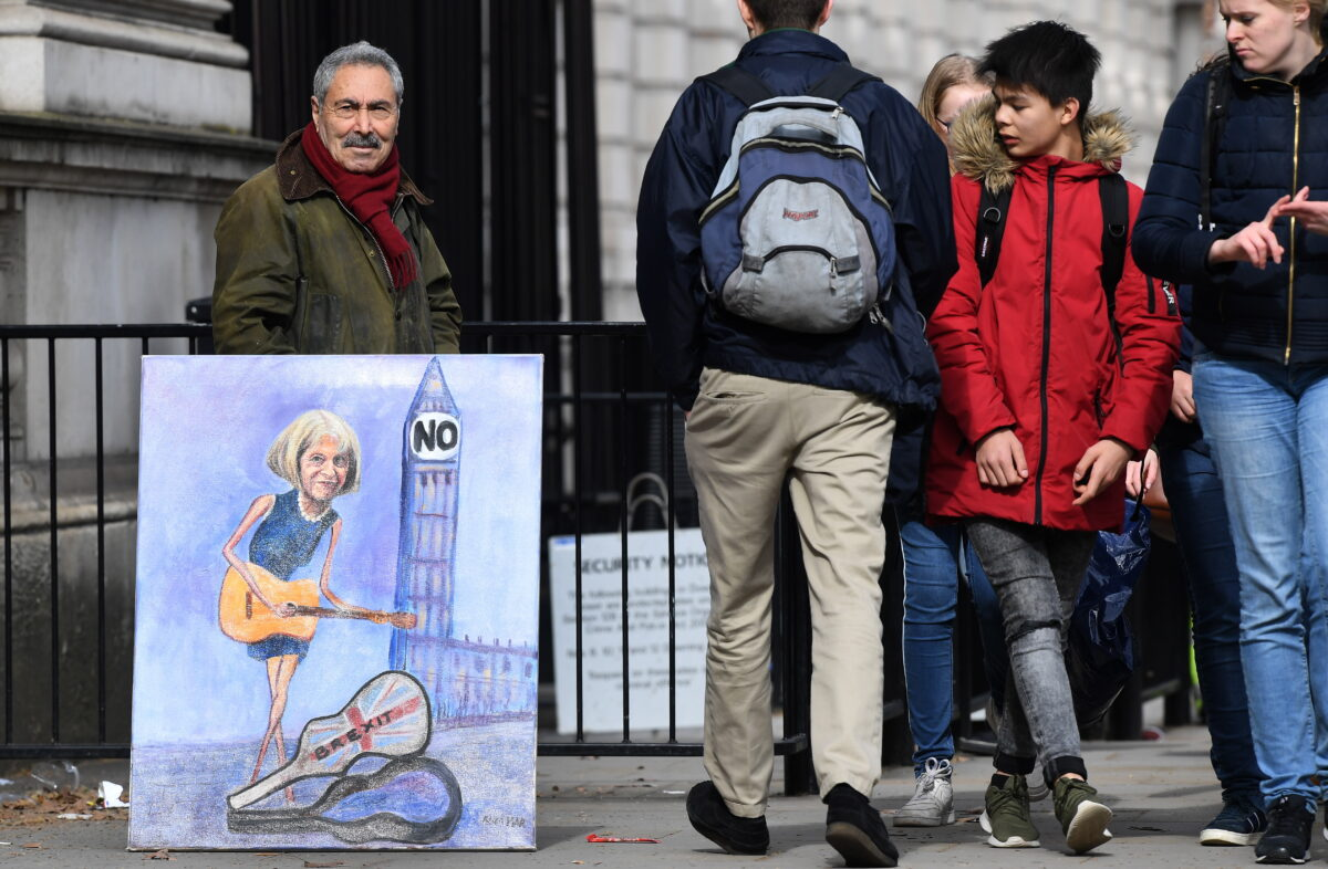 epa07433679 Political satire artist Kaya Marr (L) with his painting of British Prime Minister Theresa May outside Downing Street in London, Britain, 13 March 2019. British parliament will vote on stopping no-vote Brexit. The United Kingdom is officially due to leave the European Union on 29 March 2019, two years after triggering Article 50 in consequence to a referendum. EPA/ANDY RAIN